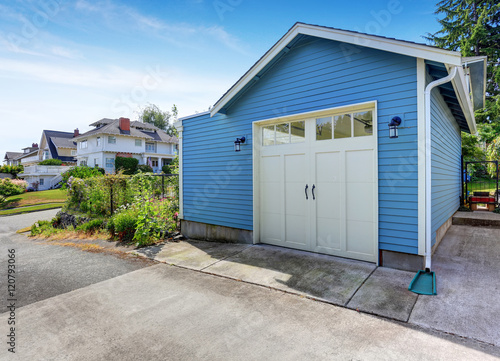 Fenced backyard with grass filled garden and small blue shed Fototapeta