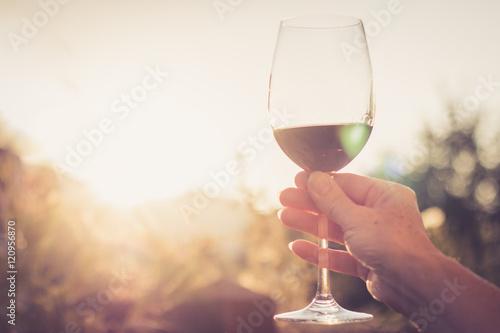 Valokuva Weinglas in Frauenhand, Abendsonne mit Sonnenstrahlen