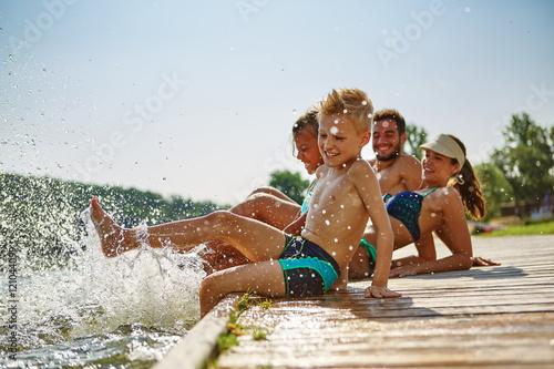 Familie hat Spaß und plantscht am Wasser #121044099