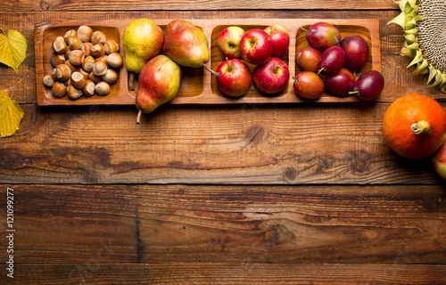 Jesienne dojrzałe owoce na drewnianym tle
