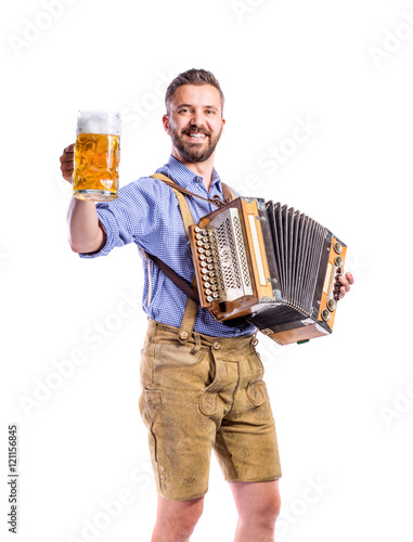 Valokuvatapetti Man in bavarian clothes holding beer, playing accordion. Oktober
