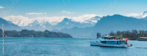 Fotografia Ferry boat with red swiss flag carry passengers on Lake Lucerne (Vierwaldstattersee) Switzerland