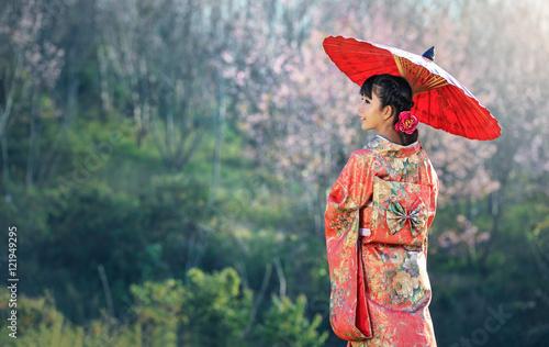 Asian woman wearing traditional japanese kimono, sakura background Fototapeta