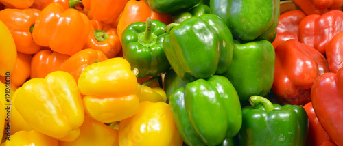 Fotografia Fresh yellow, orange, green and red organic bell peppers capsicum on display for sale at local farmer's market departmental store