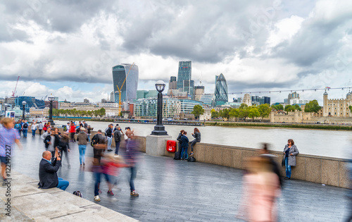 Foto Blurred image of tourists walking along river Thames in London,
