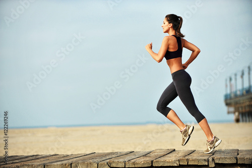 Photo Attractive fit young woman running on Santa Monica Beach boardwalk pacific ocean
