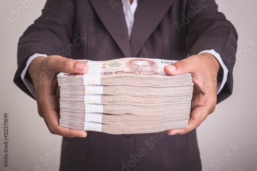 Hand giving Thai banknotes. Studio shot isolated on grey backgro Fototapeta