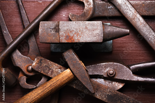 Photo Old rusty rugged anvil and other blacksmith tools.