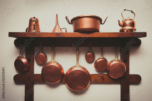 Vintage copper cookware collection on wooden shelf