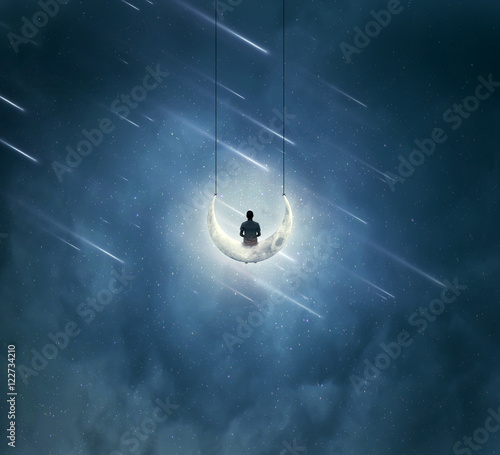 Surreal background with a lonely boy sitting on a crescent moon, as a swing, over a starry night sky with falling comets