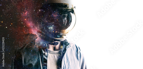 Stampa su Tela Casually dressed sad looking man in a large helmet with bright stars and galaxies projected on the shield and behind his back with white background in front of him
