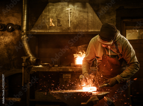 Stampa su Tela The blacksmith forging the molten metal on the anvil in smithy