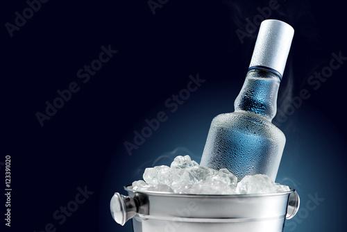 Obraz na płótnie Bottle of cold vodka in bucket of ice on dark background