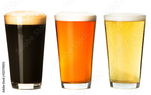 Photo Three foamy pints stout ale pilsner lager beer isolated on white background for