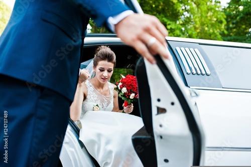 Fotografia Groom open door of limousine and take hand to bride