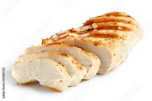 Partially sliced grilled chicken breast with black pepper and rock salt.