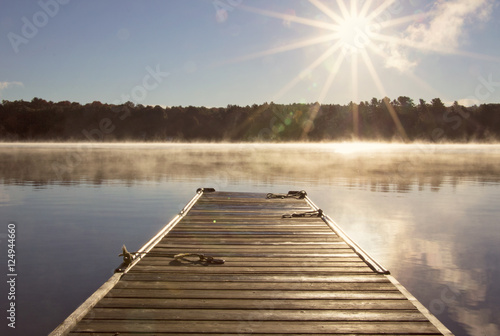 Canvas Cottage Dock  over looking the clam lake water on a misty morning with the sun s