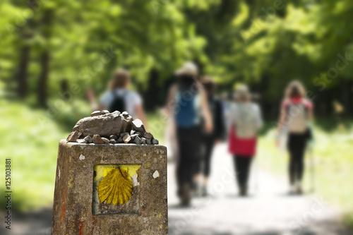 shell scallop sign mark with unfocused pilgrims  in Way of St James, Camino de S Fotobehang