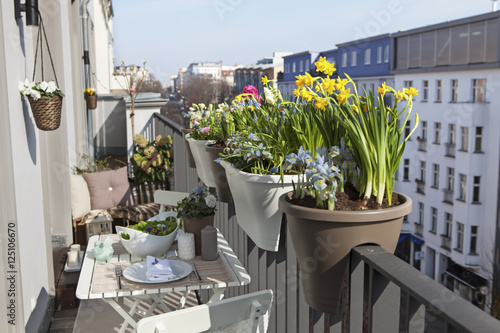 potted spring flowers on a sunny balcony in the city Fototapete