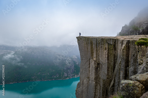 Fotomural Tourist standing at Prekestolen rock's edge.