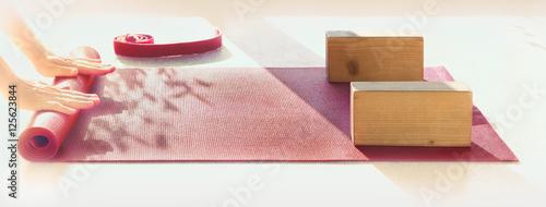 Fototapeta premium Mężczyzna przygotowuje matę i przybory do zajęć jogi.