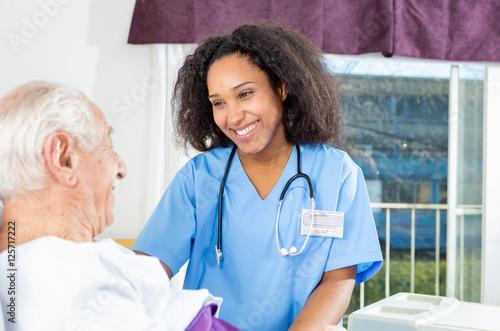 Fototapeta Caregiving nurse happy with elder patient in hospital bed