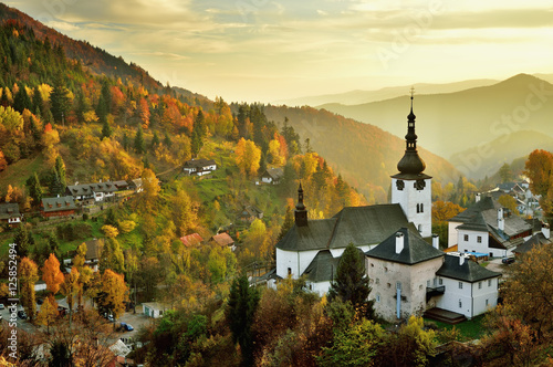 Fall in Slovakia. Old mining village. Historic church in Spania dolina. Autumn colored trees at sunset.
