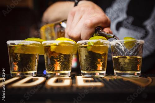 Obraz na plátně Barman pours tequila closeup club