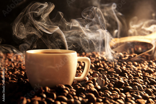 Roasted coffee beans with cup on dark background