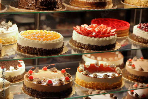 Stampa su Tela Different types of cakes in pastry shop glass display