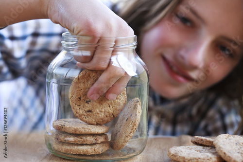Valokuva Young boy eating a cookie from the jar