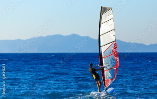 Recreational Water Sports. Windsurfing. Windsurfer Surfing The Wind On Waves In Ocean, Sea. Extreme Sport Action.  Sporting Activity. Healthy Active Lifestyle. Summer Fun Adventure. Hobby