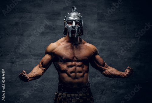 Fototapeta Muscular man in a gladiator silver helmet.