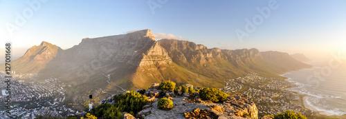 Fototapeta premium XXL panorama Góry Stołowej i pasma górskiego Dwunastu Apostołów widziana z Głowy Lwa w pobliżu Signal Hil w wieczornym słońcu. Camps Bay po prawej stronie, miasto Kapsztad po lewej stronie. Afryka Południowa.