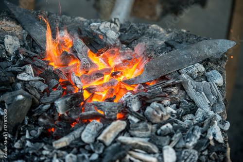 Blacksmith heats a blank for the knife in hot coals in the forge, close-up Fototapeta