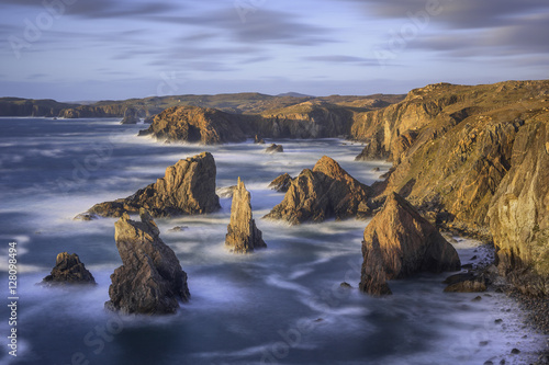 Obraz na płótnie Cliffs and stack rocks in sea at sunset, Harris and Lewis, Scotland
