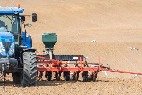 Fototapeta Tractor harrowing the field
