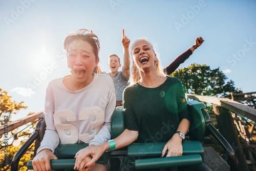 Enthusiastic young friends riding amusement park ride Fotobehang