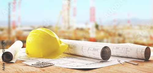 Elmetto giallo da operaio con progetti in cantiere