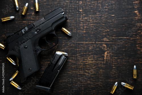 Carta da parati Gun and ammunition on dark wooden table. top view