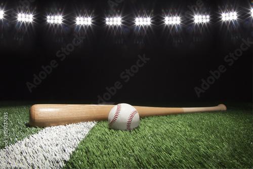 Baseball and bat at night under stadium lights on grass field