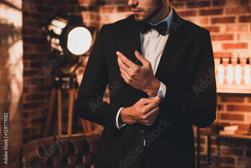 Canvas Print Close up of stylish man in black suit fastening cufflinks in lof