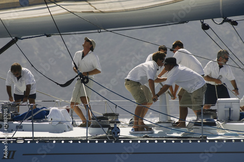 Foto Side view of crew members working on sailboat