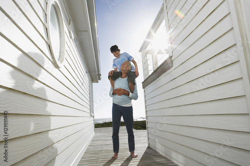 Canvas Print Full length of grandfather carrying grandson on shoulders between beach houses