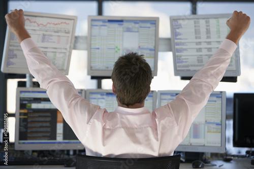 Billede på lærred Rear view of stock trader with hands raised looking at multiple computer screens