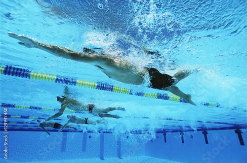 Four swimmers swimming together in a line during race Fototapeta
