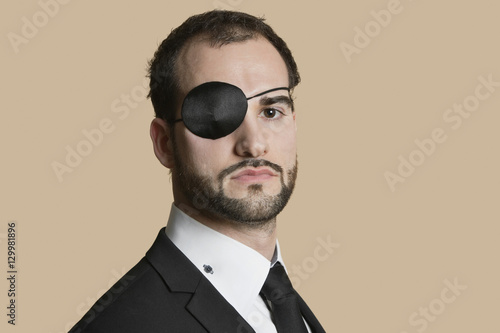 Portrait of a young businessman with eye patch over colored background Fototapeta