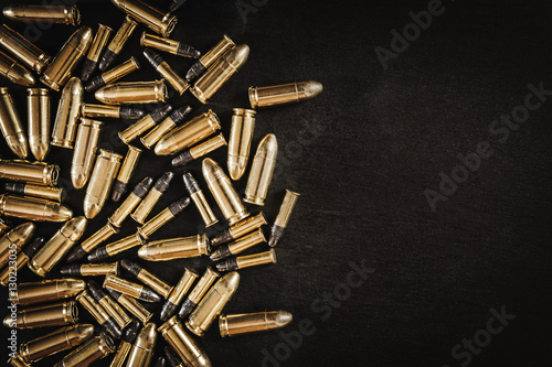 bullets from the gun placed on a black wooden table Fototapeta