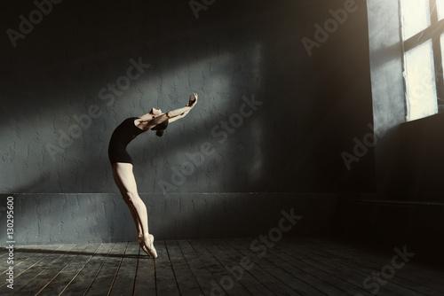 Flexible ballet dancer stretching in the dark lighted studio Fotobehang