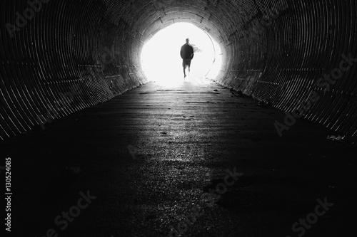 Valokuva light at the end of the tunnel with silhouette of man